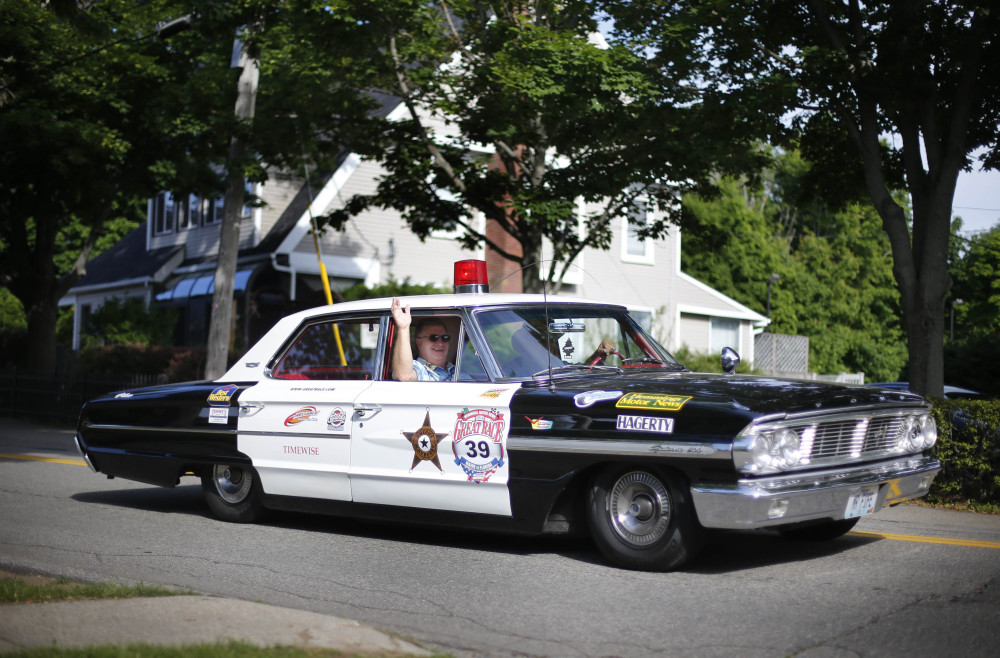 "Photos by Robert F. Bukaty/The Associated Press Navigator Gerald Schawrtz, of Jonesburg, Mo., waves to spectators from the passenger seat of ""Barnie,"" a 1964 Ford Galaxie police car driven by Bob Selleriek, of Jonesburg, Mo., on Saturday in Ogunquit."