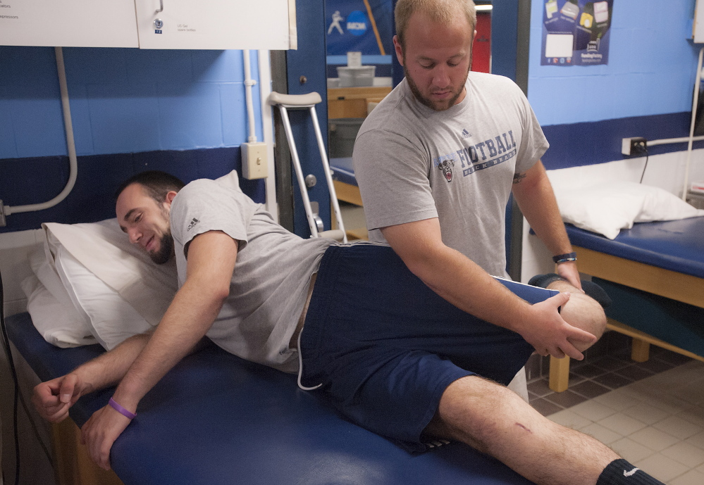 "University of Maine trainer Ben Randall works on the left knee of Kurt Massey, a defensive end who tore his ACL during spring practice. ""It's been kind of bad,"" Massey said of the loss of summer income and the medical bills his family's insurance carrier faces."
