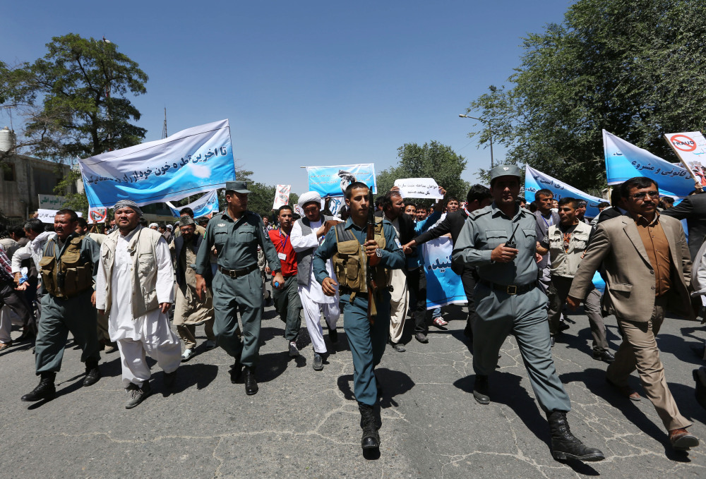 Afghan police officers secure the area as supporters of presidential candidate Abdullah Abdullah hold a protest in Kabul, Afghanistan, on Saturday.