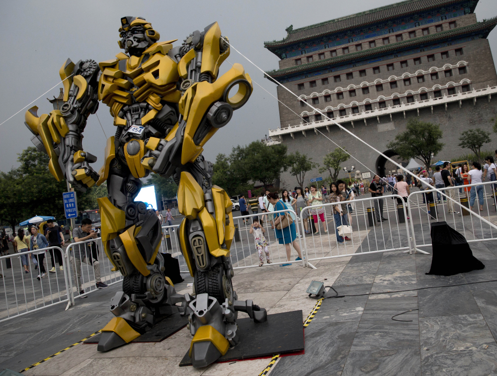 "A child looks at a replica model of Transformers character Bumblebee in Beijing, as part of a promotion of the movie ""Transformers: Age of Extinction"" on Saturday."