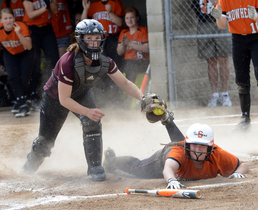 Skowhegan's Tara Bernard slides safely into home ahead of the tag by Thornton Academy catcher Aleisha Cross, capping a four-run first inning for the Indians.