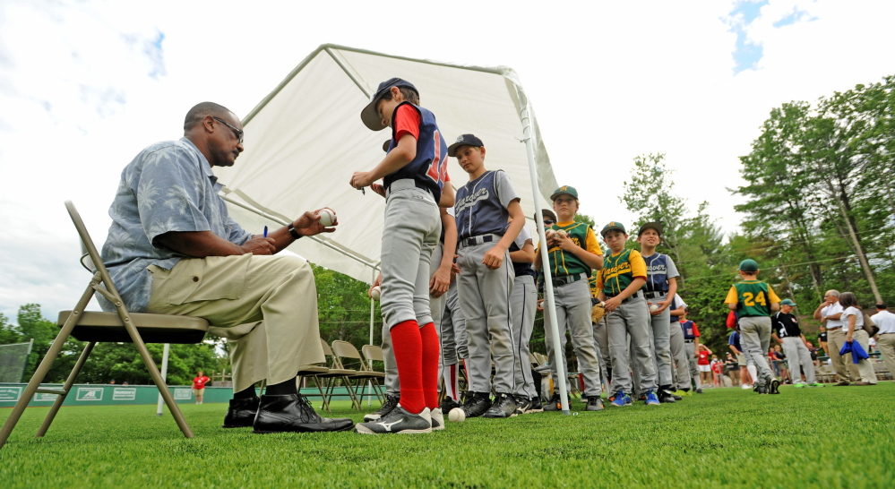 Jim Rice signs baseballs for players during the dedication of Little Fenway Park on Saturday.