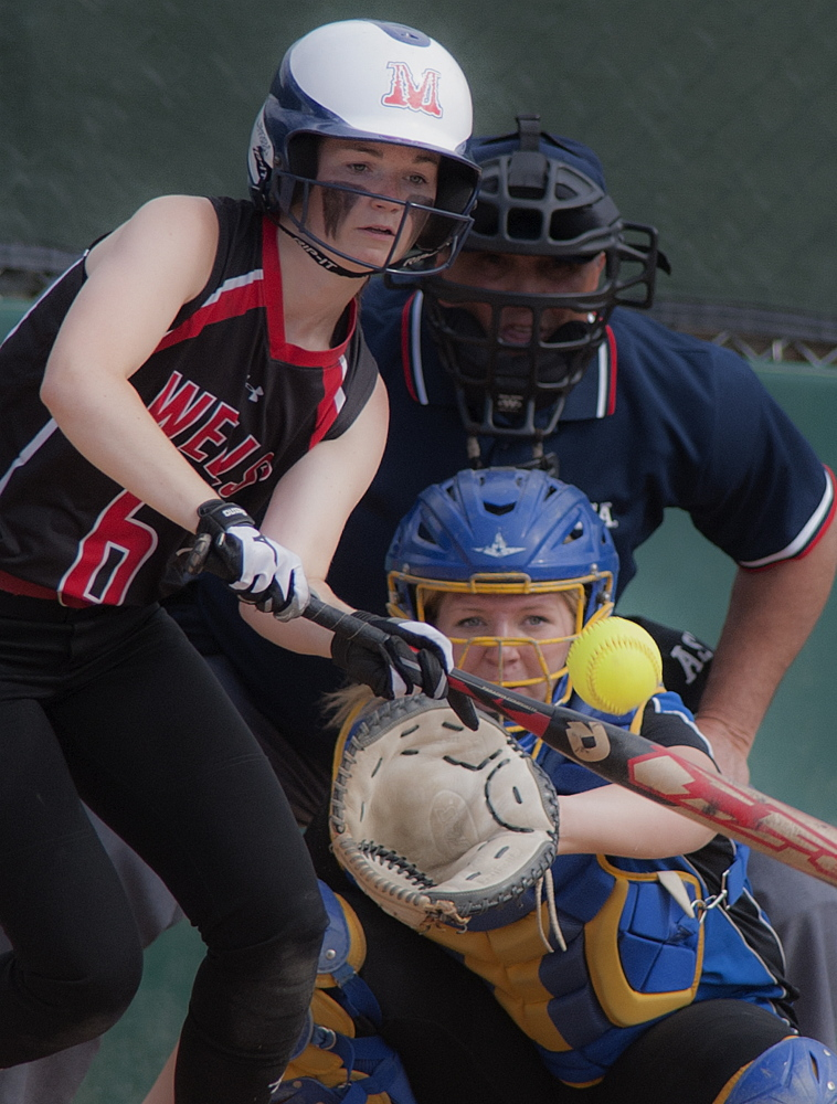 Alison Duplisea of Wells drops a bunt in front of Hermon catcher Shaniah Haskell during the Class B softball state championship game Saturday in Brewer.