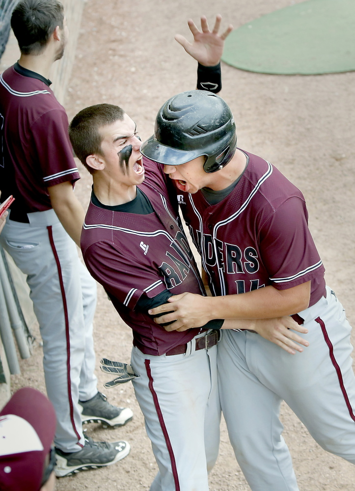 Colin Pineo, right, of Washington Academy is congratulated by teammate Kyle Taylor after Pineo scored the Raiders' third run in the first inning against Sacopee Valley during the Class C state championship game Saturday in Standish. Washington won, 7-1.