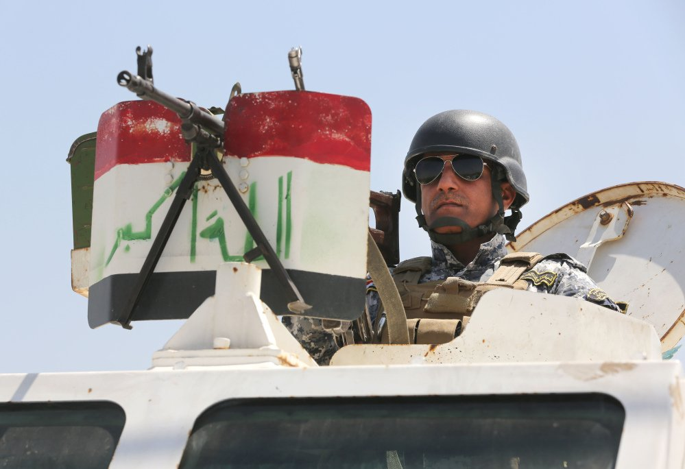 An Iraqi federal policeman standing on top an armored vehicle secures a checkpoint in Baghdad, Iraq, on Sunday. Sunni militants have seized another town in Iraq's western Anbar province, the fourth to fall in two days, officials said Sunday, in what is shaping up to be a major offensive in one of Iraq's most restive regions.