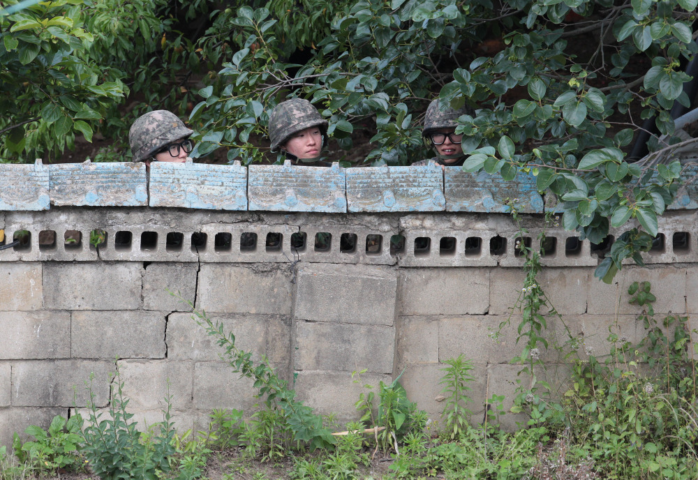 South Korean army soldiers hide behind a wall of a private house during a gunfight with a South Korean conscript soldier who is on the run after a shooting incident in Goseong, South Korea, on Sunday.