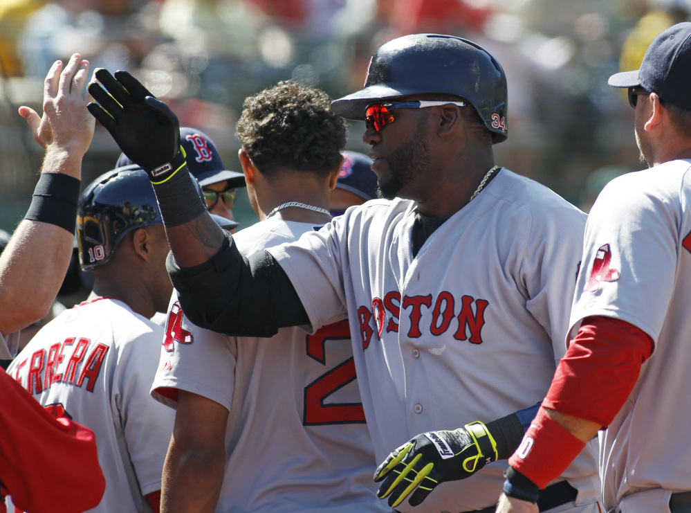 Boston Red Sox designated hitter David Ortiz is greeted at the dugout after hitting the game-winning home run against the Oakland Athletics in the 10th inning Sunday.