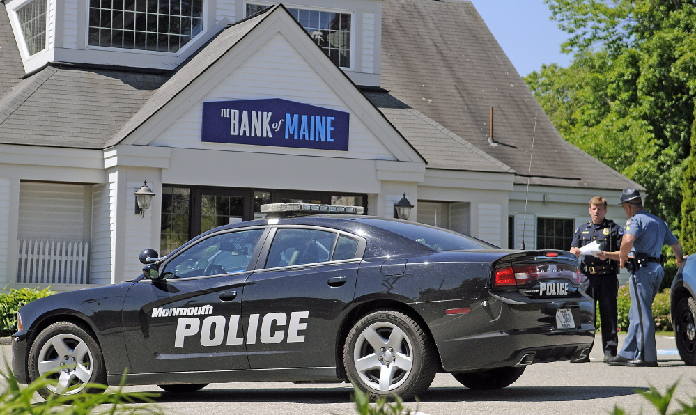 Police confer Monday outside the Bank of Maine branch in Hallowell after it was robbed Monday.