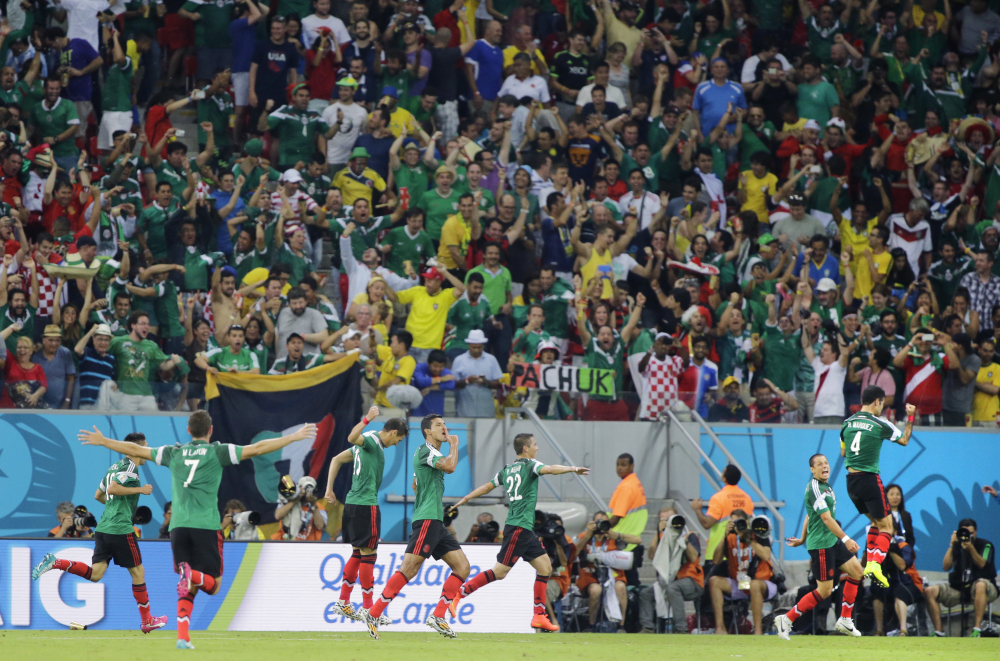 Mexico's Rafael Marquez, right, celebrates with teammates after scoring the opening goal during the group A World Cup soccer match between Croatia and Mexico in Recife, Brazil, Monday, June 23, 2014.