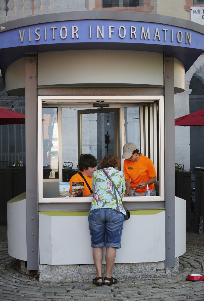 Robert Chason, left, and Becky Wartell help a visitor at the Portland Downtown District information kiosk at Tommy's Park on Monday.