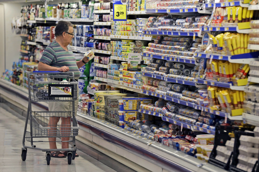 In this June 17, 2014 photo, a shopper looks at an item in the dairy section of a Kroger grocery store in Richardson, Texas.