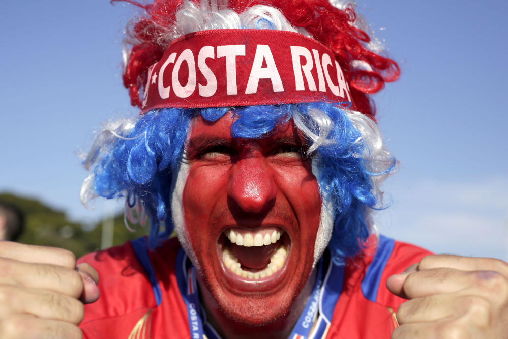 A supporter celebrates Costa Rica's finishing first in what many considered the World Cup's toughest group after a 0-0 draw against England.