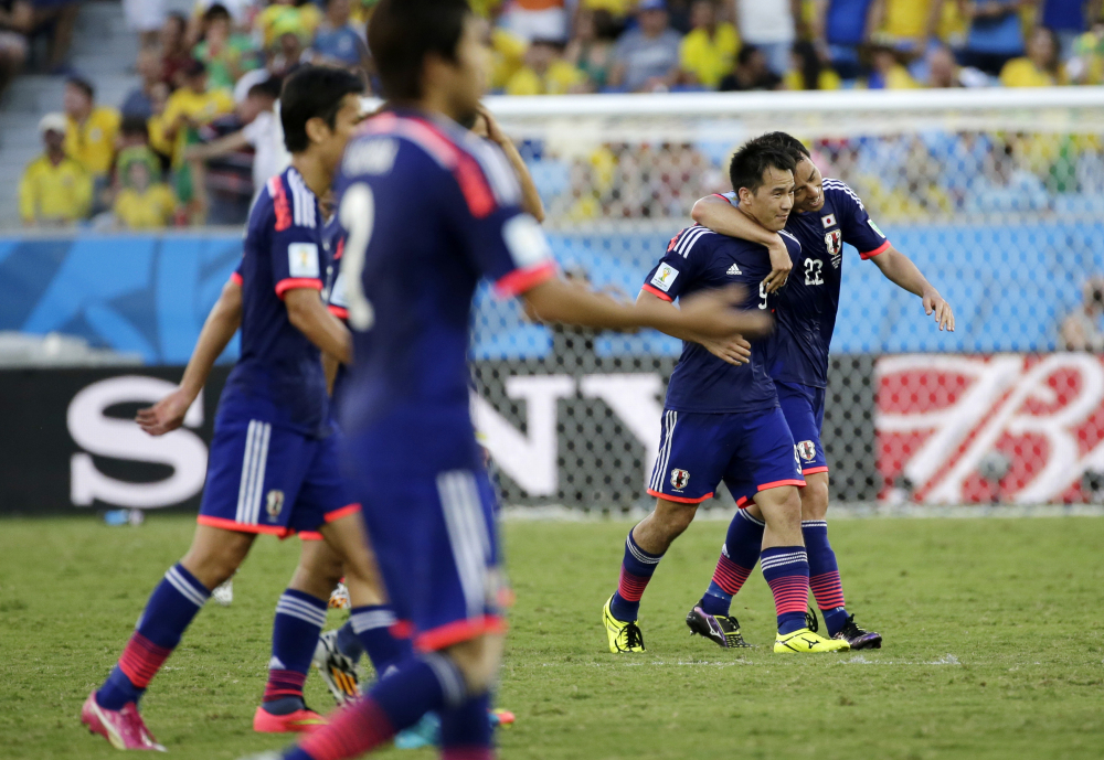 Japan's Shinji Okazaki second from right, celebrates with teammate Japan's Maya Yoshida after scoring during the group C World Cup soccer match between Japan and Colombia.