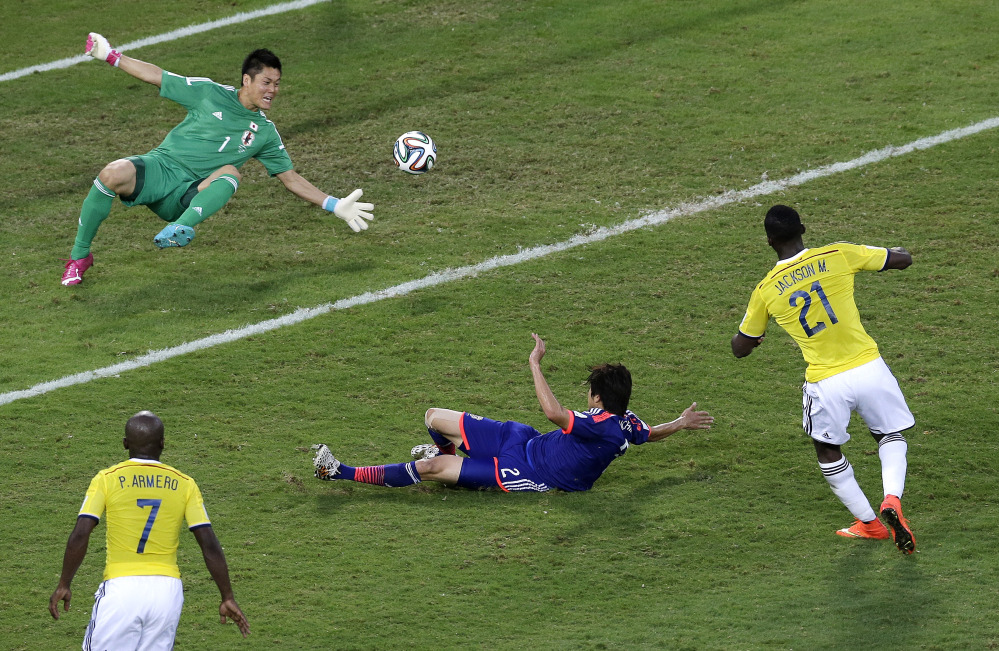 Colombia forward Jackson Martinez, right, scores past Japan defender Atsuto Uchida and goalkeeper Eiji Kawashima during the second half of a group C World Cup soccer match in Cuiaba, Brazil, Tuesday, June 24, 2014.