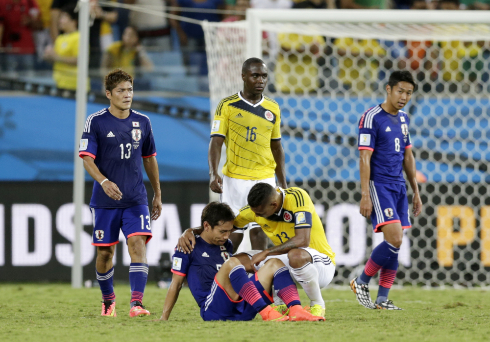 Colombia's Fredy Guarin, right comforts Japan's Yuto Nagatomo after the group C World Cup soccer match.