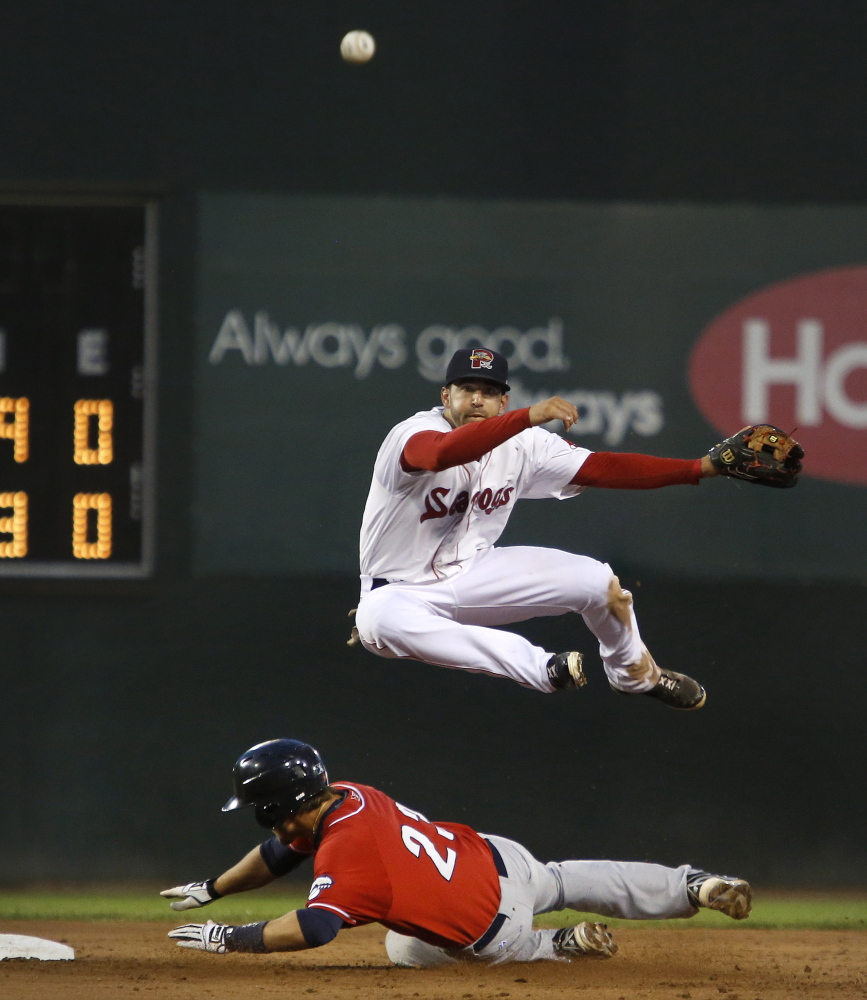 Deven Marrero of Portland leaps over New Hampshire baserunner Kevin Nolan while completing a double-play to end the top of the sixth inning Tuesday in Portland. The Fisher Cats won 5-1. Derek Davis/Staff Photographer