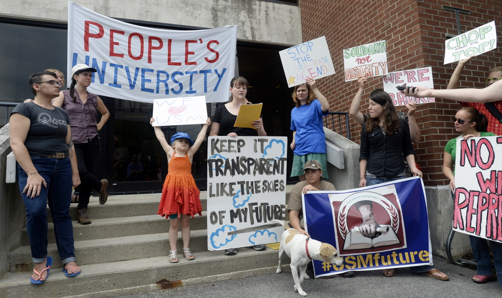 University of Southern Maine student Sarah Victor, center speaks during a protest as her daughter and other protestors hold signs at the University of Southern Maine on Wednesday.