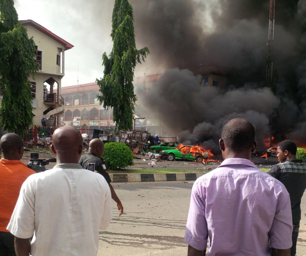 People watch as smoke fills the sky after an explosion rocked a shopping mall Wednesday in Abuja, Nigeria.