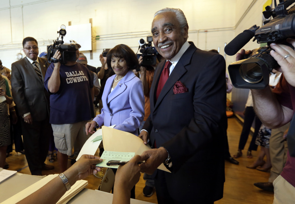 U.S. Rep. Charles Rangel, D-N.Y., accompanied by his wife, Alma Rangel, receives his ballot to vote in the congressional primaries Tuesday in New York.