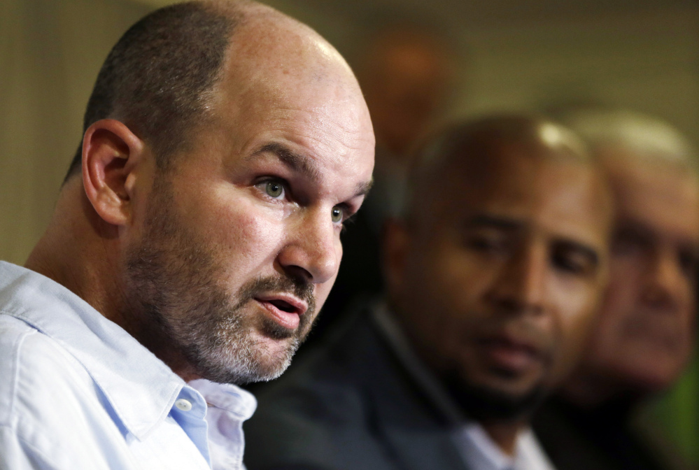 In this April 9, 2013 file photo, former NFL player Kevin Turner, left, speaks during a news conference in Philadelphia, as former players Dorsey Levens, center, and Bill Bergey listen. The NFL agreed Wednesday, June 25, 2014, to remove a $675 million cap on damages from thousands of concussion-related claims after a federal judge questioned whether there would be enough money to cover as many as 20,000 retired players. The plaintiffs include Turner, who played for the Philadelphia Eagles and New England Patriots and is now battling ALS.
