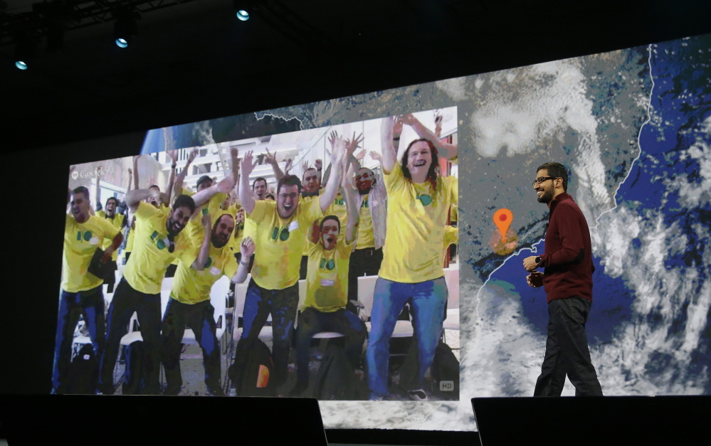 Sundar Pichai, right, Google's senior vice president who oversees Android  and Chrome software divisions, smiles as a group watching live from Brazil is projected on the screen during the Google I/O 2014 keynote presentation in San Francisco on Wednesday.