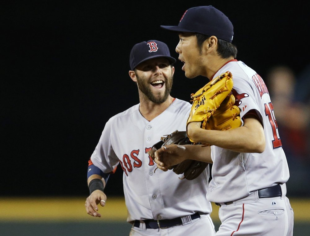 Boston Red Sox closer Koji Uehara, right, is greeted by Dustin Pedroia after the Red Sox defeated the Seattle Mariners 5-4 Wednesday in Seattle.