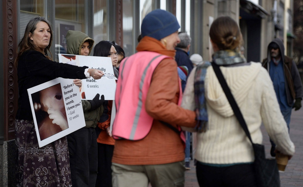 As Leslie Sneddon of Richmond offers literature near Planned Parenthood in Portland, a volunteer escorts a woman past protesters on Nov. 15, 2013. Three days later, the City Council approved a buffer zone.