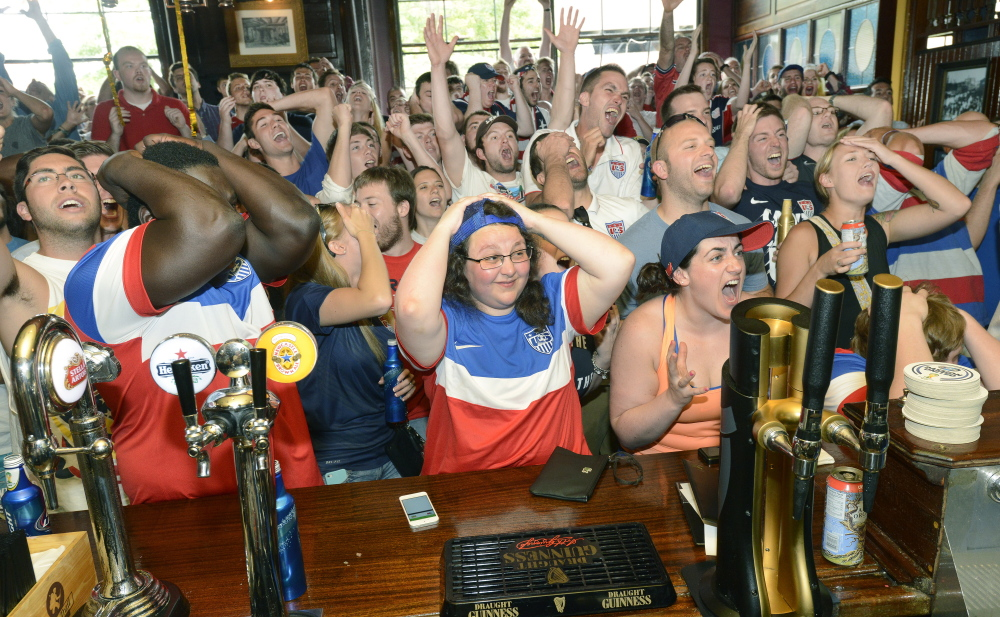 Richard Agbortoko of Cameroon, his arms covering his face, reacts to a missed goal with Jessica Donovan, center, of Portland, and Jenna Fabiano of South Portland and the rest of the crowd at RiRa's in Portland  during the World Cup match that pitted the United States and Germany in Brazil on Thursday.