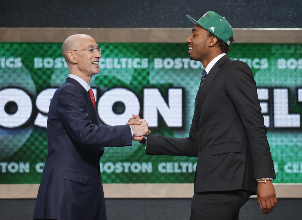 Kentucky's James Young, right, is greeted by NBA Commissioner Adam Silver after being selected as the 17th overall pick by the Boston Celtics during the 2014 NBA draft, Thursday, June 26, 2014, in New York. (AP Photo/Jason DeCrow)