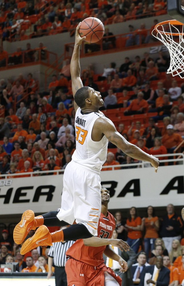 Oklahoma State guard Marcus Smart goes up for a dunk in front of Texas Tech forward Jordan Tolbert in a February game in Stillwater, Okla.