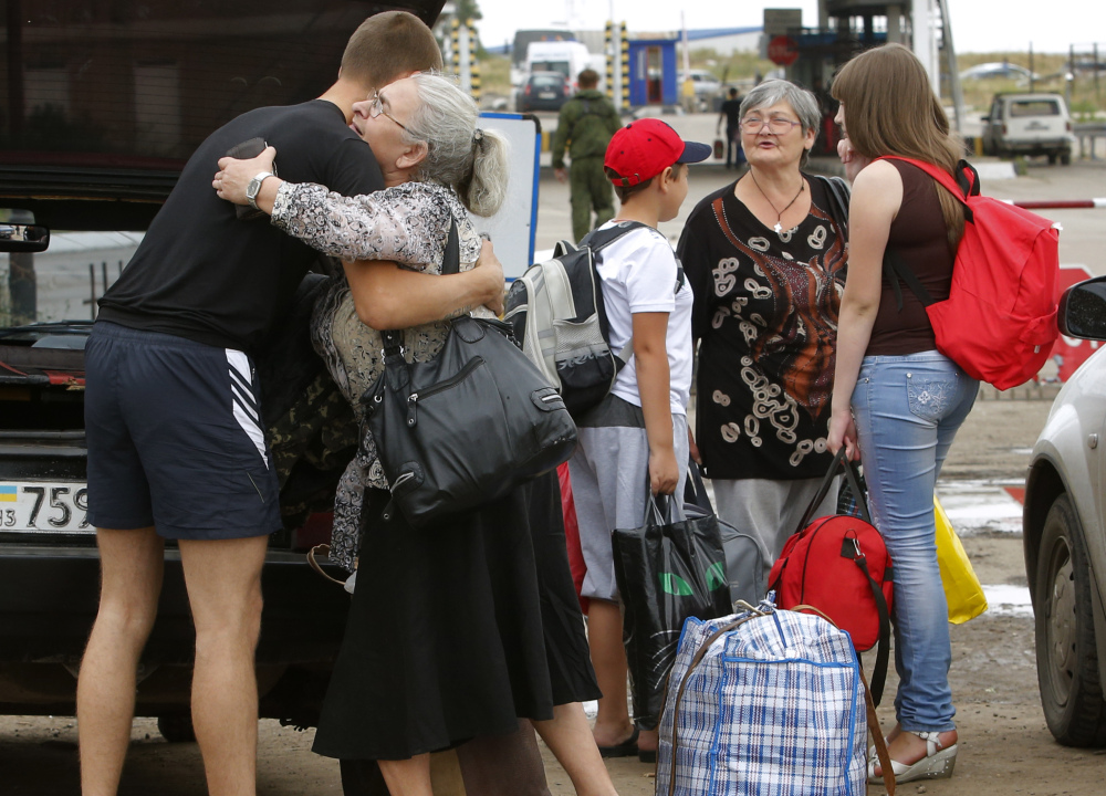 A man says goodbye to his relatives as they prepare to cross the border into Russia at the Ukrainian-Russian border checkpoint in the Luhansk region of Ukraine on Thursday