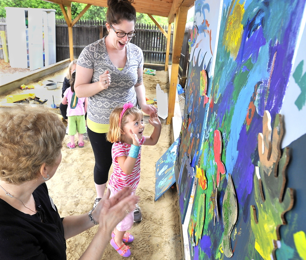 Evelyn Kirby, 3, expresses her joy Thursday after successfully putting fish-shaped cutouts onto a painting of the ocean at Children's Odyssey, an art-language camp in Portland for pre-schoolers. Speech-language pathologist Laurie Mack, left, from Northeast Hearing and Speech Center and Jacklyn Peters, a fourth-year art education student at the University of Southern Maine, share in Evelyn's excitement.