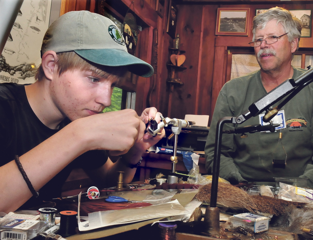 Teenager Sam Kenney concentrates as he learns how to tie a fly under the tutelage of Jim Dunbar of Winslow at the trout camp in Solon on Thursday.