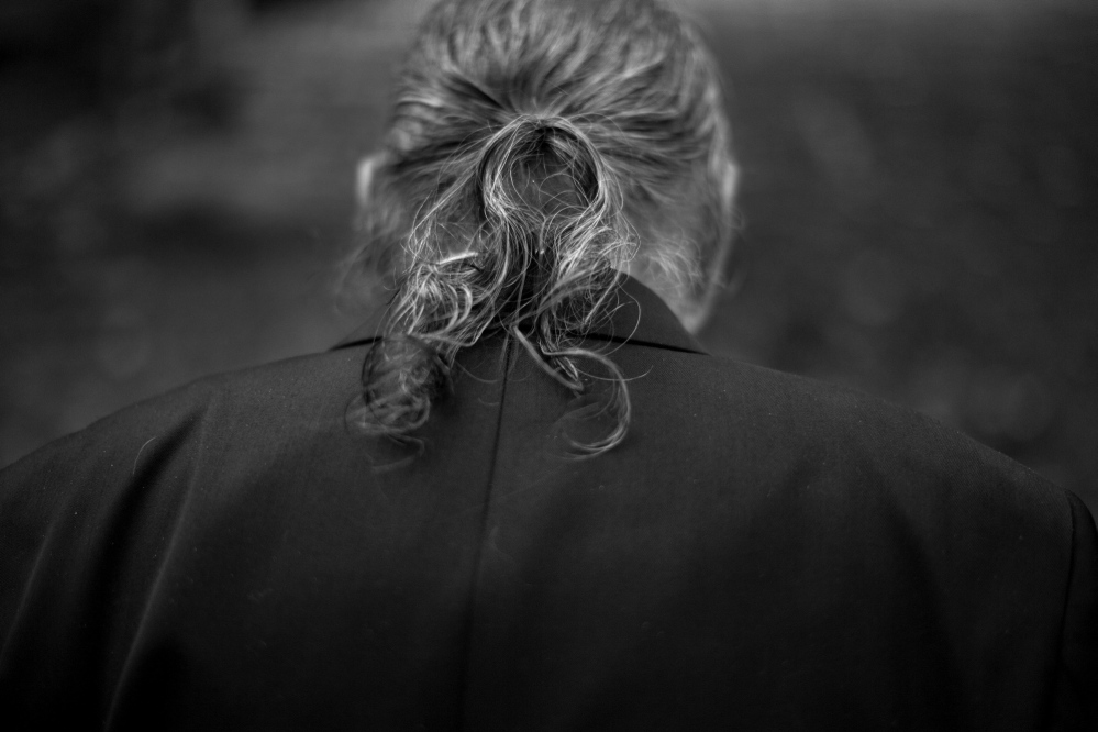 black and white image of a man in a jacket with a ponytail facing away from the camera