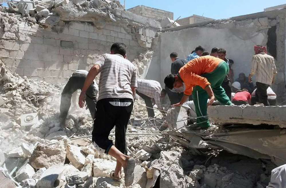 This photo provided by the anti-government activist group Syrian Observatory for Human Rights shows Syrians inspecting the rubble of destroyed houses following a Syrian government airstrike in Aleppo on Wednesday, June. 25, 2014. Syrian government warplanes struck a series of targets in the northern city that is a stronghold of an al-Qaida splinter group, killing and wounding several people, opposition activists said.