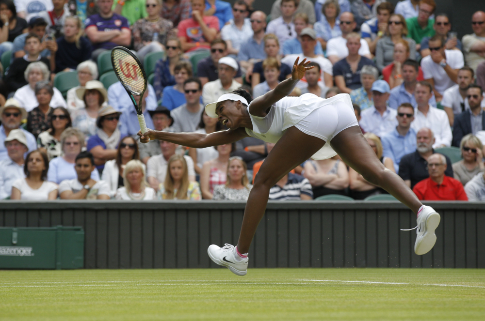 Venus Williams of U.S. reaches for a return to Petra Kvitova of the Czech Republic during their women's singles match in Wimbledon, London, Friday, June 27, 2014.