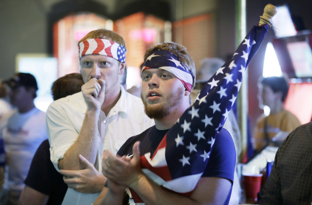 Aaron Todd, right, and Zach Crabtree, both of Knoxville, Iowa, react as they watch the World Cup Soccer match between the United States and Germany at a bar, Thursday, June 26, 2014, in West Des Moines, Iowa. Thousands of eager Americans set work aside on Thursday – with or without their bosses' OK – to watch the key World Cup match. Todd and Crabtree said they took the day off to watch the match.