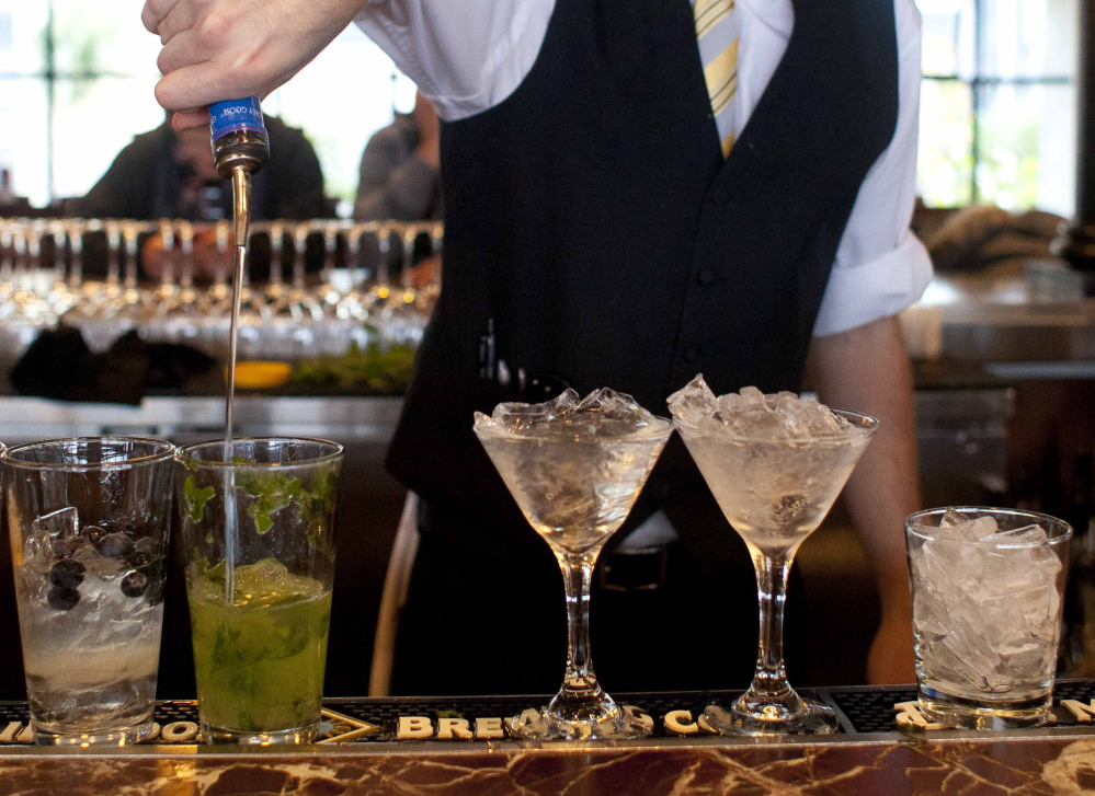 A bartender prepares alcoholic drinks at a restaurant. Researchers who prepared a recent report defined excessive drinking as five or more drinks per occasion for men and four for women.