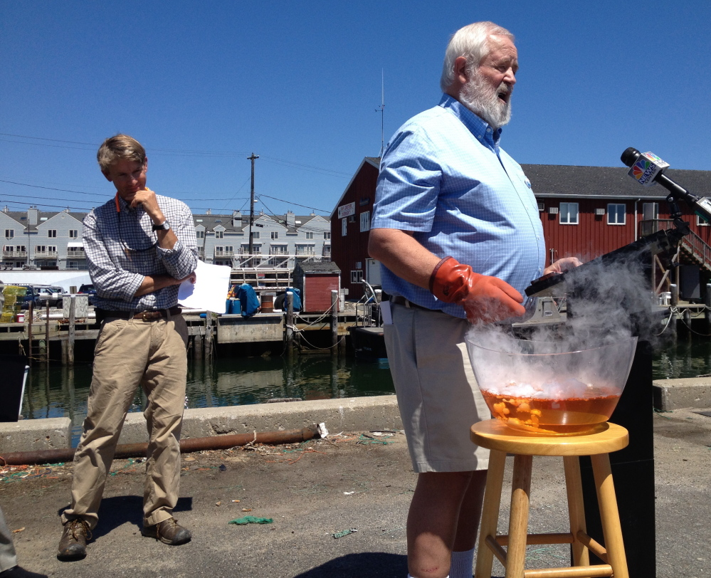 Eric Horne, left, an oyster farmer from Freeport, takes in a demonstration by Casco Baykeeper Joe Payne, who uses chemicals to show the acidity levels in a bowl of seawater during a news conference Friday on the Portland waterfront. A new state panel will study the impact of ocean acidification on the shellfish industry.