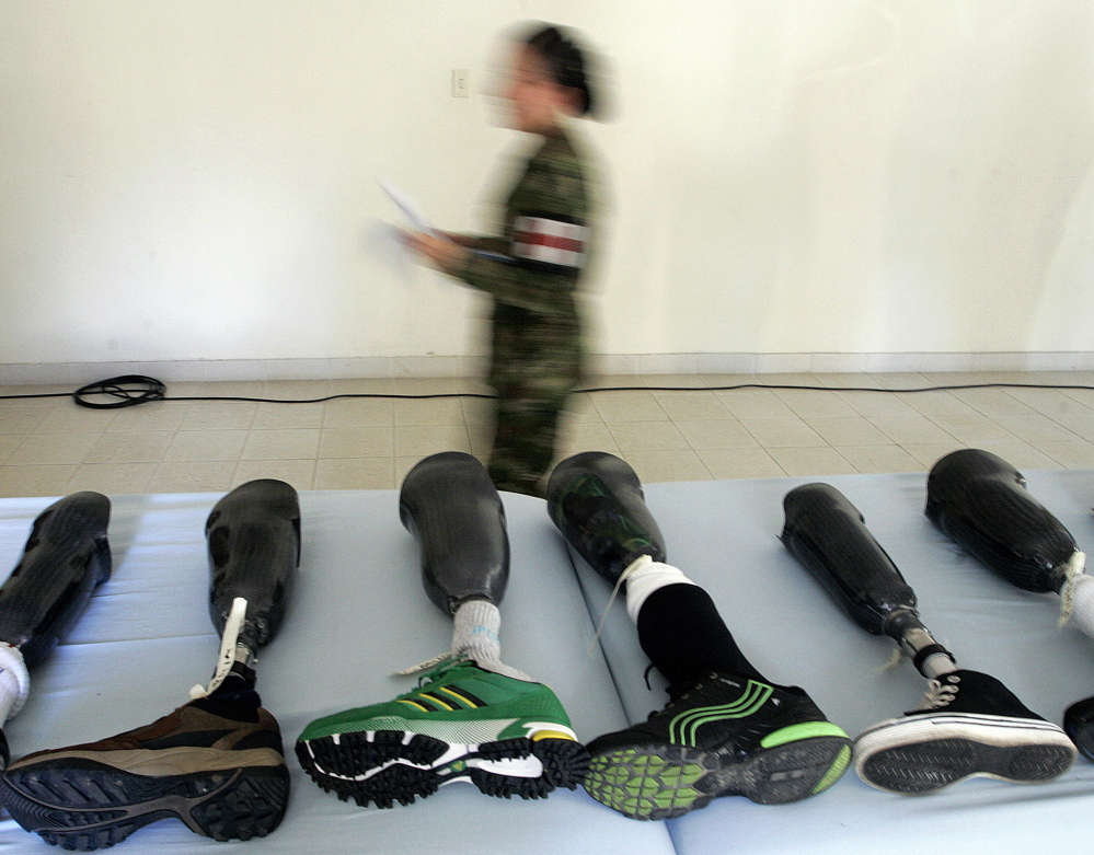 A member of the Colombian army walks past prosthetic limbs to be delivered to victims of land mines, in Medellin in 2011. File Photo/The Associated Press