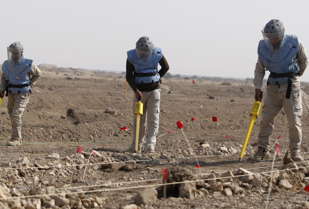 Above, members of the Iraqi Mine and Unexploded Ordnance Clearance Organization work to find land mines in the Shatt-al-Arab district, in Iraq's southern city of Basra, in 2012. File Photo/The Associated Press