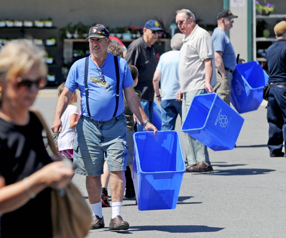People make their way back to their vehicles with free recycling bins from Ecomaine at Elm Plaza in Waterville on Friday.
