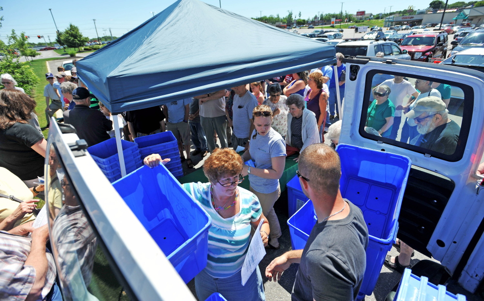 Ecomaine workers distribute free recycling bins to the public at Elm Plaza in Waterville on Friday.