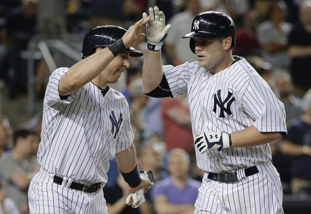 New York Yankees' Brian McCann, right, is greeted at home plate by Mark Teixeira after hitting a two-run home run in the 8th inning against the Boston Red Sox. The Yankees won 6-0.