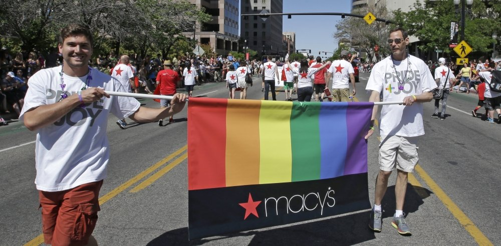 Workers carry a Macy's banner during the gay pride parade in Salt Lake City this month. Corporations such as Starbucks, Delta Air Lines and General Motors have increased visibility at pride events around the country this summer.