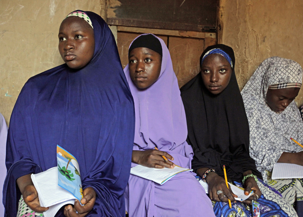 Maimuna Abdullahi, left, listens as she and others attend school in Kaduna, Nigeria. She is one of thousands of divorced girls in Nigeria who were married as children and then got thrown out by their husbands or simply fled.