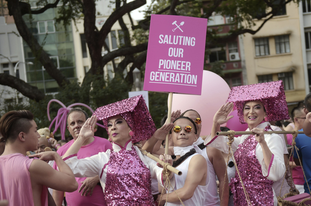 Gay activists dressed as female construction workers or Samsui Women and laborers from the colonial period pose in mock salute at Saturday's rally in Singapore.