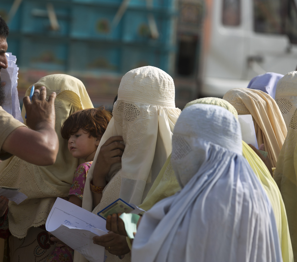 A Pakistani soldier checks documents of displaced tribal women in Bannu.
