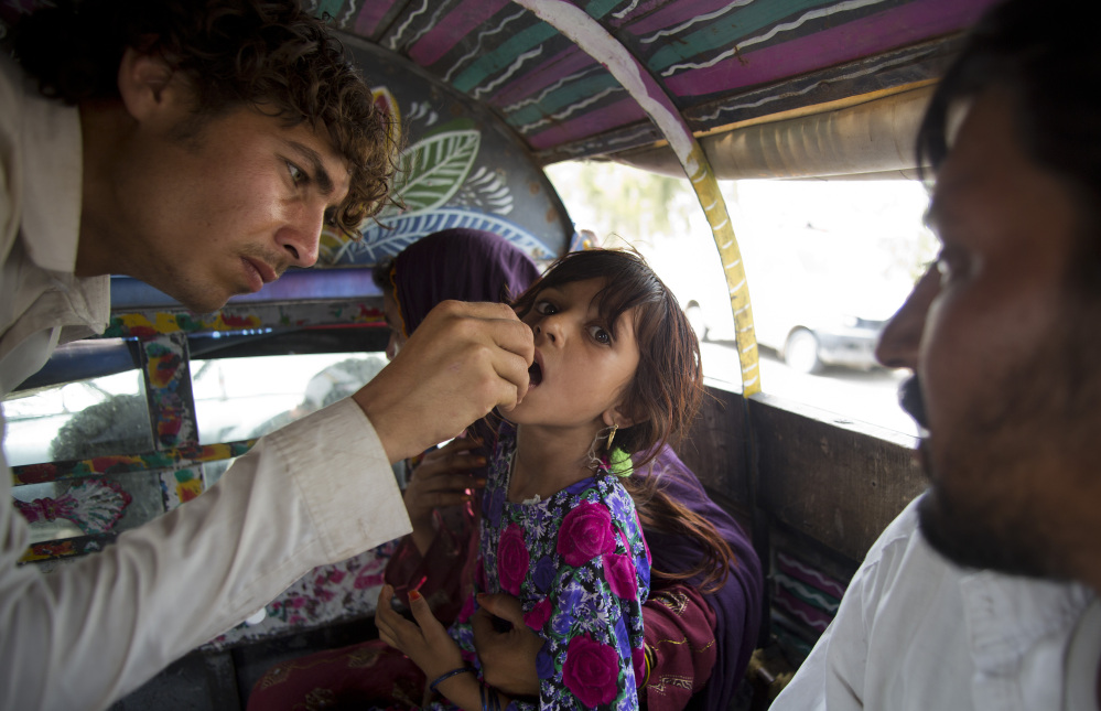 A Pakistani volunteer gives the polio vaccine to a displaced girl in Bannu. North Waziristan became a hotbed of polio infections after the Taliban banned immunizations.