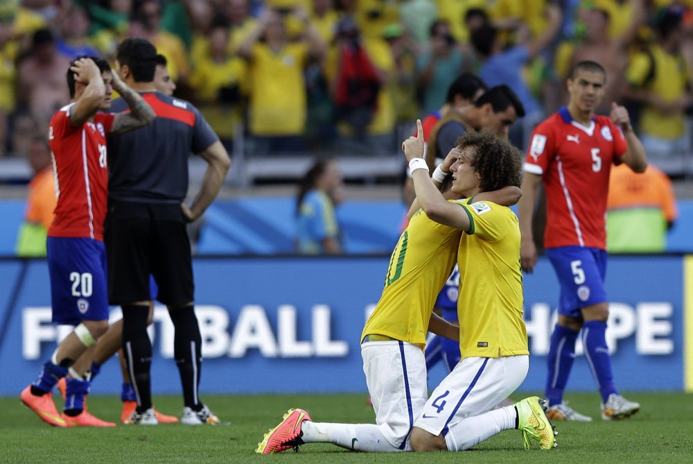 Brazil's David Luiz, right, embraces Neymar after a shootout victory over Chile on Saturday that sent their team to the World Cup quarterfinals. Luiz and Neymar each scored during penalty kicks as Brazil won with a 3-2 advantage after the match ended 1-1 at Belo Horizonte, Brazil.